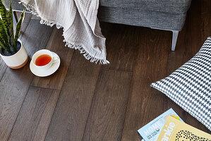 Teetasse, Plaid, Kissen und Zeitschriften auf dunklem Holzboden