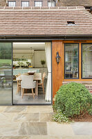 View from terrace through open glass sliding doors into open-plan kitchen