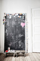 Photos stuck on chalkboard next to two wooden stools