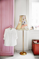 White blouse hung on pink wardrobe and standard lamp in child's bedroom