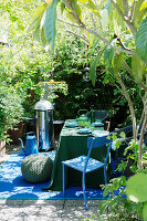 Barbecue and table set in green and blue on summery terrace