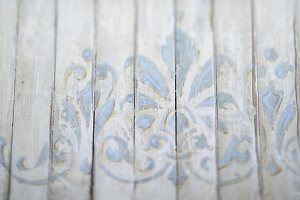 Wooden surface painted with ornate pale blue pattern