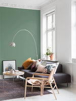 Scandinavian-style living room with green wall in period building