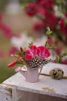 Posy of geraniums, fuchsia, feather and apple twig in tiny watering can