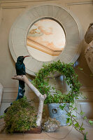 Stuffed bird and wreath of ivy below round mirror