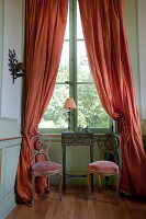 Side table and two upholstered antique chairs in front of window with long coral-red curtains