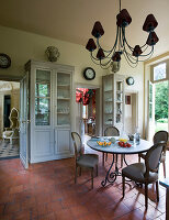 Glass-fronted cabinet, round table and upholstered antique chairs in breakfast room