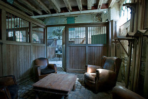 Vintage leather armchairs and coffee table in old stable