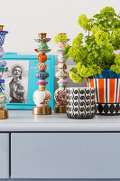 Photo, candlesticks, candle lantern and houseplant on grey sideboard