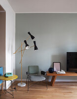 Designer standard lamp and retro telephone on side table in seating area