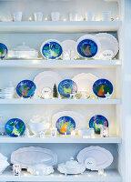 Weißes Porzellan und blaue Dekoteller mit Wintermotiven dekoriert mit Lichterketten in Regal