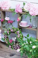 Kranz aus Spierstrauch-Blüten, Nelken in Fläschchen und Rosenblüten