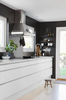 Moderne weiße Küchenzeile an schwarzer Wand