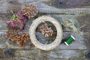 materials for an autumn wreath: dried hydrangea flowers, sedum plant, straw horns, hay, and binding wire