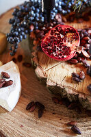 Halved pomegranate, roasted almonds and cheese on wooden board