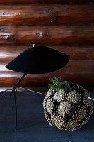 Ball of pine cones below black table lamp
