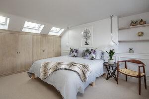 Schlafzimmer in Weiß mit beigefarbener Einbauschrankwand unter Dachschräge mit Fenstern