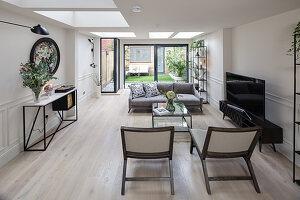 Langgestrecktes Wohnzimmer mit Oberlichtfenstern und Fensterfront zum Garten