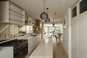 White kitchen with narrow island counter in elongated open-plan interior