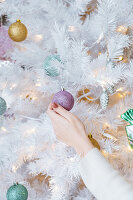 Female hanging Christmas decorations on artificial white fir tree at home