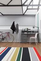 Striped rug and desk below steel ceiling girders in loft apartment
