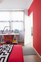 Bed and desk in teenager's bedroom with red accents
