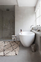 Free-standing bathtub and Oriental accessories in modern, grey and white bathroom