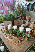 Rural Advent decoration with candles in an elongated Advent wreath, drawers with cones and branches