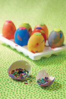 Brightly painted Easter eggs with glitter in eggshell in foreground