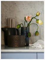 Poppy buds coming into flower in rustic vase next to candles in jug