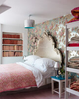 Bed with Baroque headboard against shiny floral wallpaper