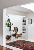 Chair and glass console table in white hallway