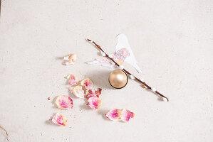 Easter arrangement: rose petals, willow catkins, gilt egg and paper birds