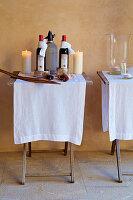 Zwei Klapptische mit weißen Läufern, Weinflaschen und Kerzen