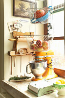 Mixer and hanging storage baskets in rustic kitchen