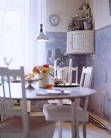 Esstisch und Stühle im Shabby Chic vor blau-weißer Wand mit Patina
