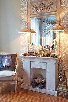 Attrappe einer Kaminkonsole mit winterlicher Deko und Spiegel
