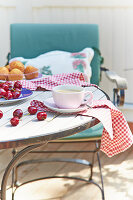 Cup of coffee, cherries and muffins on summery garden table