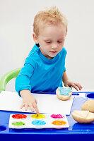 Kleiner Junge macht mit bunten Fingerfarben Kartoffeldruck