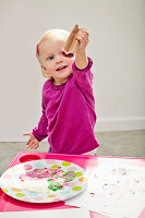 Little girl printing coloured hearts using cardboard tube