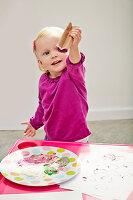 Kleines Mädchen stempelt mit Papprolle bunte Farbherzen auf Papier