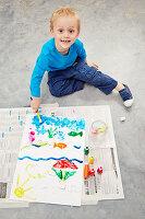 Kleiner Junge beim Bemalen der Rückseite eines Puzzles