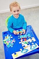Little boy with hand-painted jigsaw