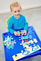 Kleiner Junge mit selbstgestaltetem Puzzle