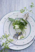 Cutlery arranged with sweet peas and lady's mantle on plate