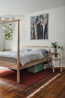 Modern wooden bed with high foot on Persian rug