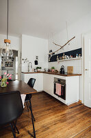 Black and white kitchen-dining room with dark wooden floor