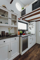 White kitchen counter below mezzanine in tiny house