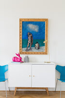 Blue painting with gilt frame above modern white sideboard