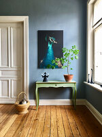 Green console table below picture of peacock on blue wall in period building